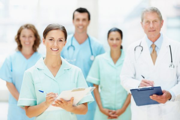 Portrait of young nurse holding notepad with her blur team in background